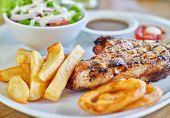 thick pork steak with gravy, salad and hand cut fries poster