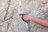 picture of sabbatical  - Praying man is putting paper with wishes during Sabbat ceremonies on Western Wall in Jerusalem - JPG