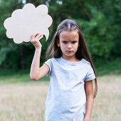 Pretty angry sad thinking little girl posing summer nature outdoor with cloud of thoughts (like in c poster