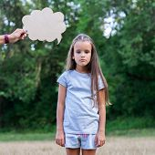 Pretty sad thinking little girl posing summer nature outdoor with cloud of thoughts (like in comic b poster