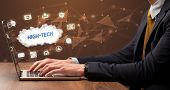 Businessman working on laptop with HIGH-TECH inscription, modern technology concept poster
