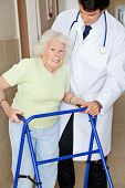stock photo of zimmer frame  - Portrait of a senior woman using walker standing by young doctor - JPG