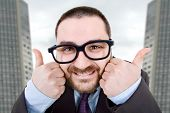 stock photo of feeling stupid  - young silly business man going thumbs up - JPG