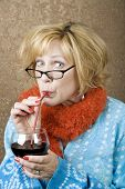 stock photo of tawdry  - Funny woman drinking wine through a straw - JPG