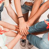 children keeping hands together as a team with friendship poster