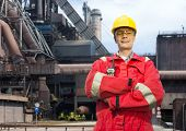 stock photo of blast-furnace  - Factory worker posing in front of a blast furnace - JPG