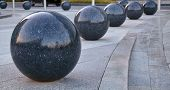 A Large Number Of Black Marble Large Balls Lined Up poster