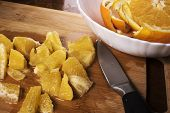 Knife Chopping Oranges Into Segments On Wooden Board. Cooking With Fruit poster
