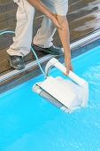African Hand Pool Cleaner During His Work. Cleaning Robot For Cleaning The Botton Of Swimming Pools. poster
