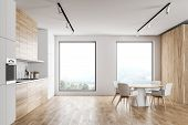 Stylish White And Wooden Kitchen With Dining Table poster