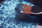 Makeup brush on blue shiny shadows. Bright shadows with glitter glitter. Macro frame of shadows. Bri poster
