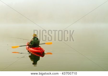 fisherman in red kayak, foggy morning