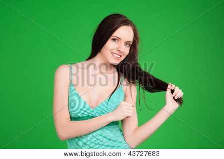 Smiling Brunette Girl Holding Her Hair Over Green Background