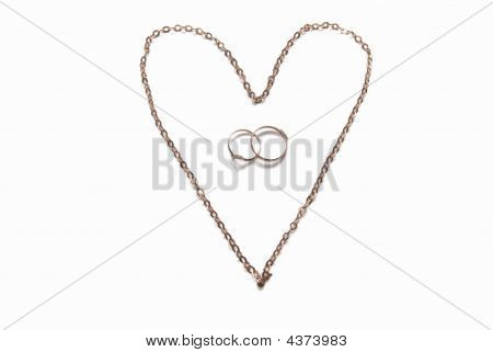 Heart Laid Out From A Gold Chain And Wedding Rings