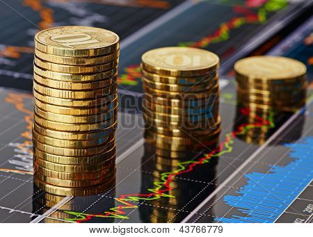 Down Trend Stacks Of Coins And Financial Chart As The Background