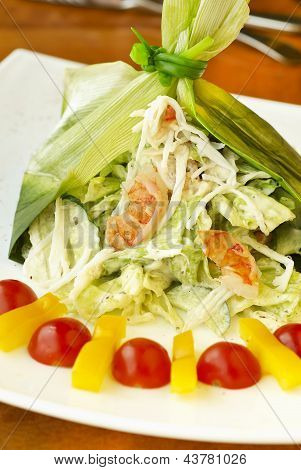 Holiday salad with crab, shrimp and vegetables in leek leaf