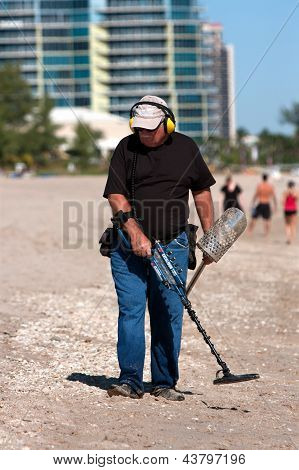 Man Combs Beach With Metal Detector