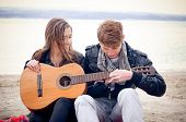 stock photo of guitarists  - Young girl with acoustic guitar and her boyfriend on the bach - JPG