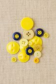 Pile Of Yellow Buttons On Hessian