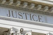 stock photo of justice  - a justice word engraved on courthouse pediment - JPG
