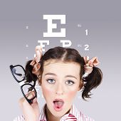 stock photo of dorky  - Funny portrait of a blind nerd woman holding glasses while struggling to read an optometry eyesight test chart - JPG