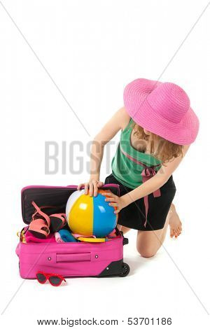 Packing the pink suitcase for the summer vacation by an young, blond woman