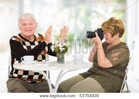 senior man refusing to be photographed by his wife at home