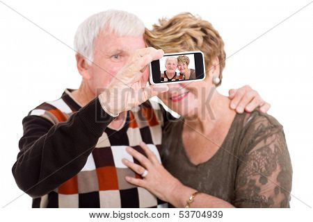 happy senior couple taking self portrait with smart phone isolated on white