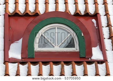 Attic Arch Window With Snow On Red Tile Roof. Old Part Of Tallinn, Estonia