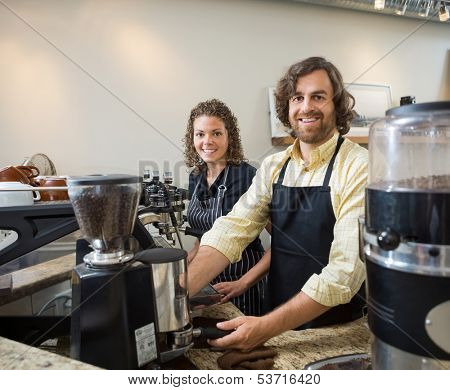 Portrait of happy colleagues working in coffeeshop