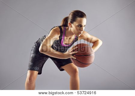 Young Woman Basketball Player On Grey Background