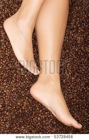 Female legs on coffee seeds. Closeup.