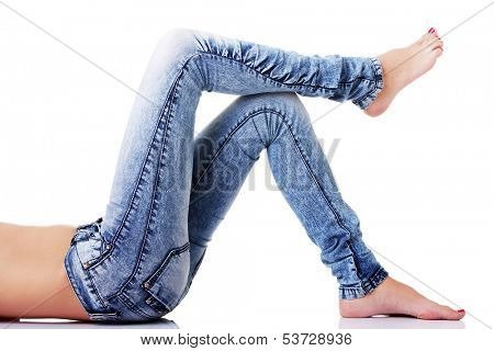 Female's legs in jeans on the floor. Side view. isolated on white.