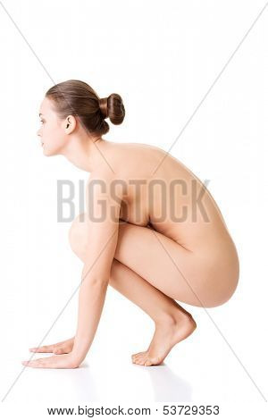 Attractive young naked woman in a crouch. Side view.isolated on white.