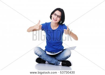 Female student with workbook on knees showing OK. Isolated on white.