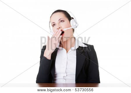 Business woman with headphones yawning. Isolated on white.