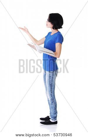 Attractive woman with workbook. Side view. Pointing on copy space. Isolated on white.