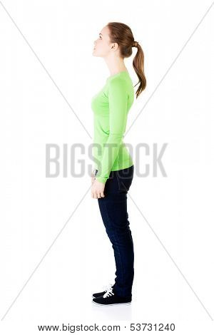 Attractive woman standing and looking up. Side view. Isolated on white.