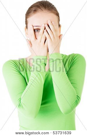 Attractive woman covering her face with both hands. Isolated on white.
