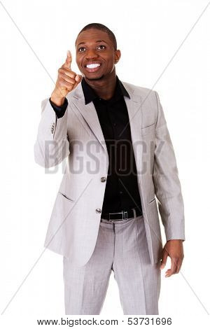 Male businessman poiting high in a smile. Isolated on white.