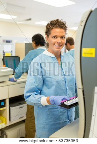 Portrait of happy female medical lab tech with sample for coagulation analysis