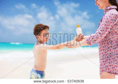 Close up of a mother applying sunblock cream on her son