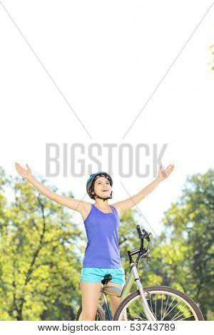 Happy female biker posing with raised hands on a mountain bike in a park