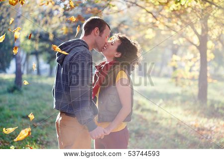 Loving Couple Kissing In The Park In The Sunlight On Trees Background