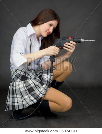 Beautiful Girl In A Skirt With A Drill