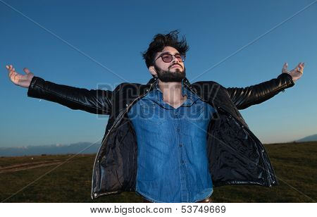 happy young man with outstretched hands looking away from the camera