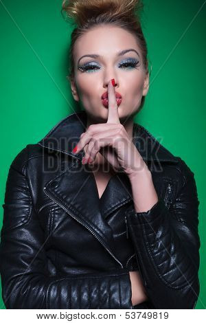 fashion woman with nice makeup and hairstyle is covering her mouth with her finger making the quiet gesture