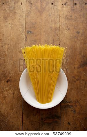 Bundle of long spaghetti on a white dish, placed on a old grungy wooden desk.
