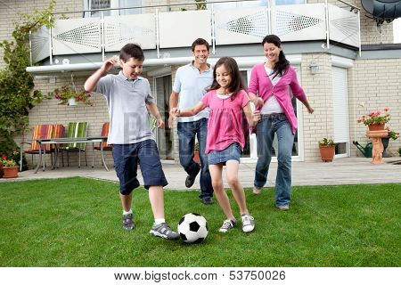 Happy Family Playing Football In Their Backyard