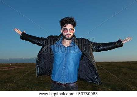 young man with open arms against blue sky, freedom concept